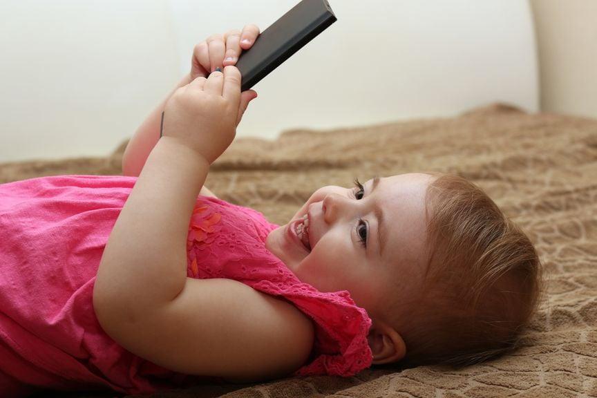 Kind spielt mit einem Natel