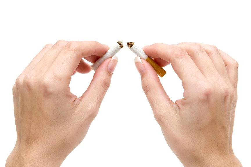 Hände brechen Zigarette auseinander