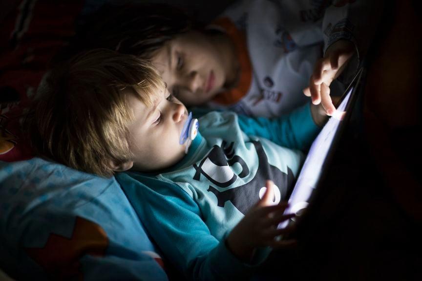 Kinder mit Tablet im Bett