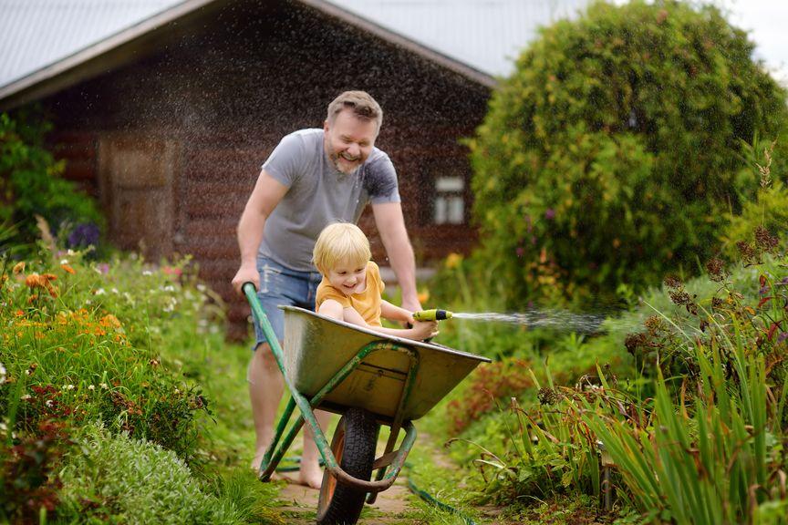 Vater schiebt Kind im Schubkarren durch den Garten