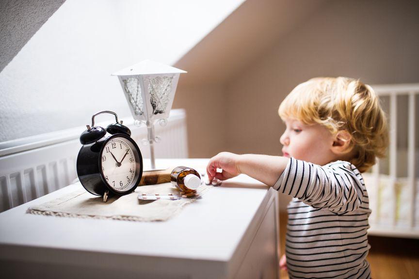 Kind greift nach Medikamenten auf dem Nachttisch