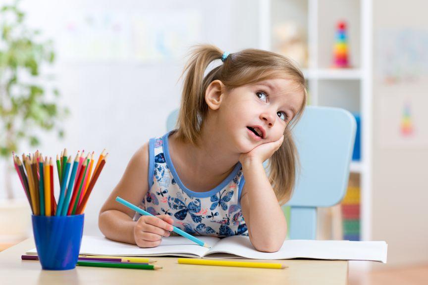 Kind beim Zeichnen, Kinn aufgestützt