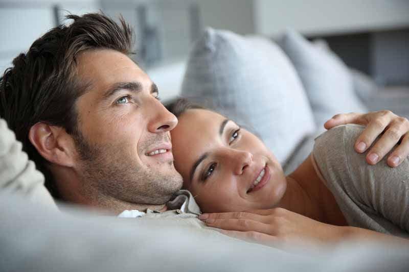 Verträumtes Paar liegt auf dem Sofa