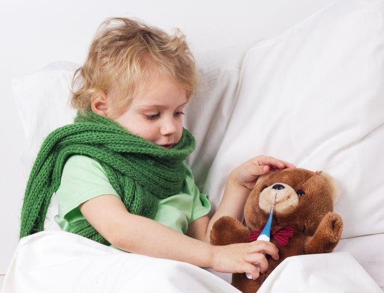 Krankes Kind mit Halstuch und Teddy
