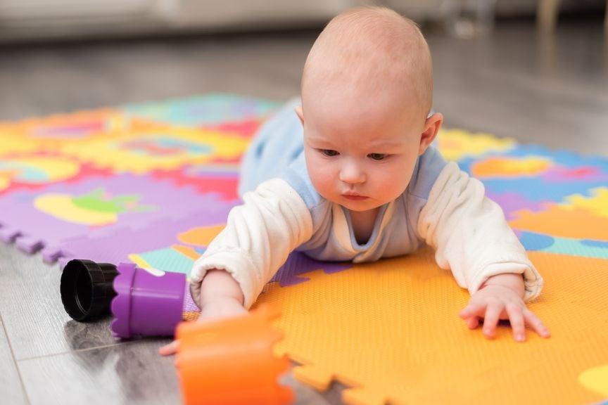 Baby liegt bäuchlings auf einer Spielmatte