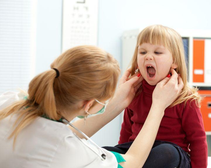 Ärztin untersucht Hals und Mund