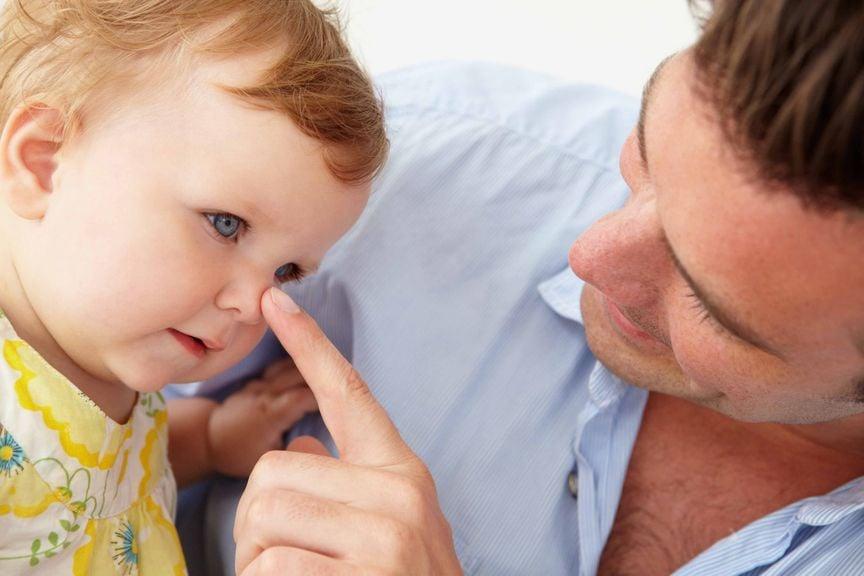 Vater stupst Baby mit dem Finger auf die Nase