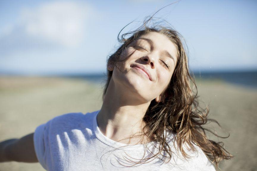 Junge, glückliche Frau am Strand