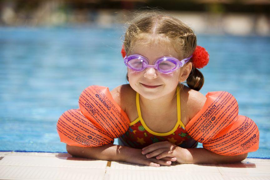 Mädchen mit Schwimmflügeln im Schwimmbad