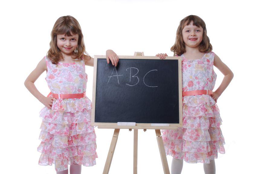 Zwillinge stehen neben Schreibtafel