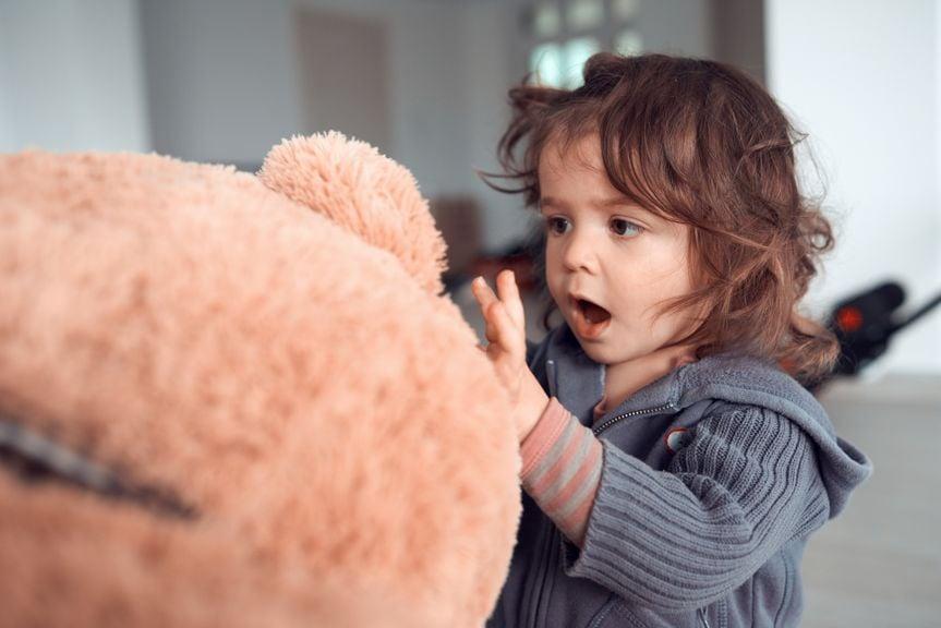 Kind spricht mit Teddybär