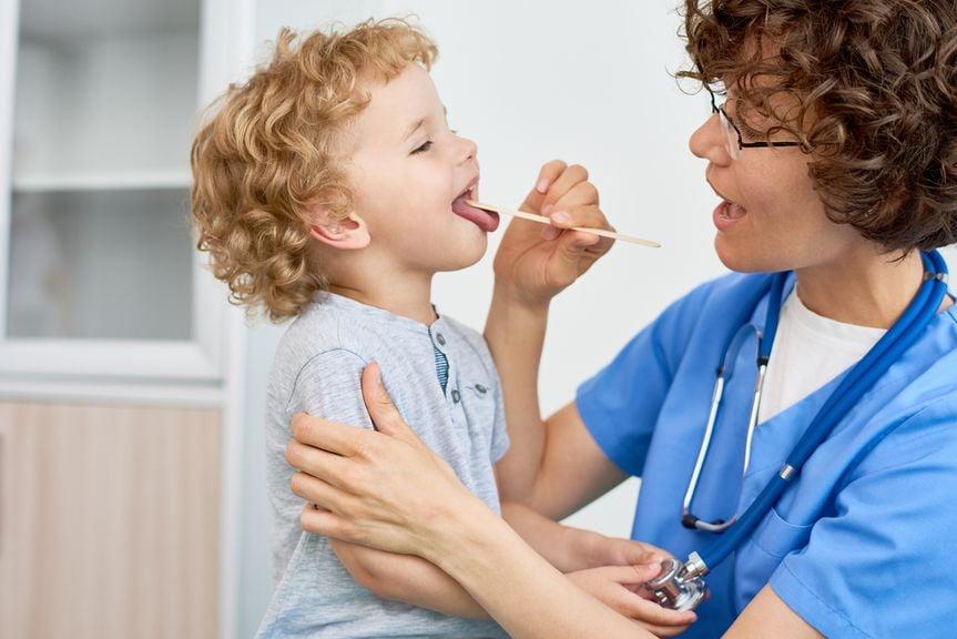 Ärztin schaut in den Kindermund