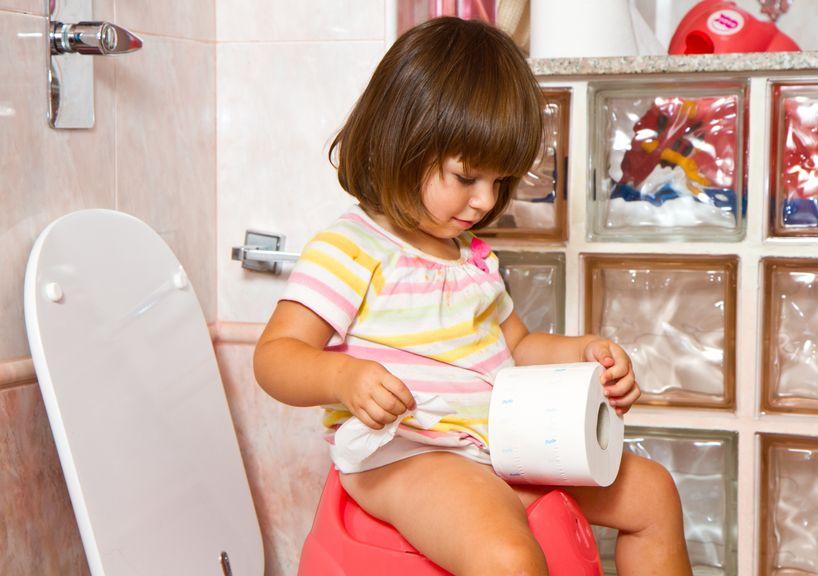 Kind auf dem Töpfchen mit WC-Papier