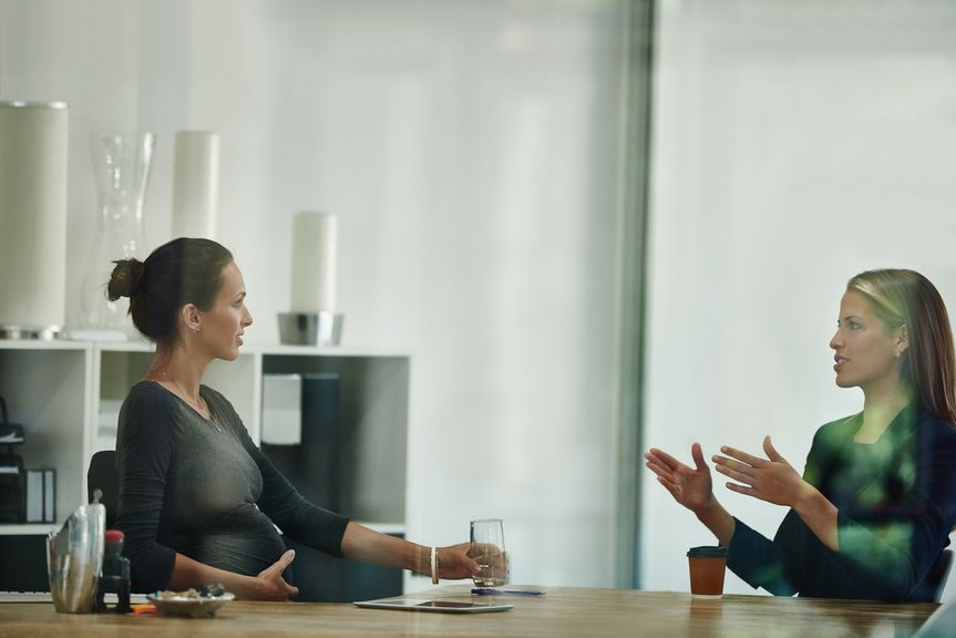 Schwangere im Büro bei der Besprechung mit einer Kollegin oder Vorgesetzten