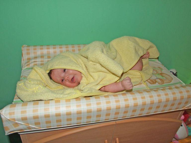 Baby im Badetuch auf der Wickelkommode