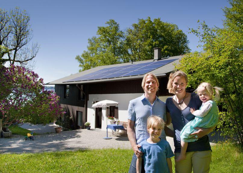 Familie mit zwei Kindern vor ihrem Haus