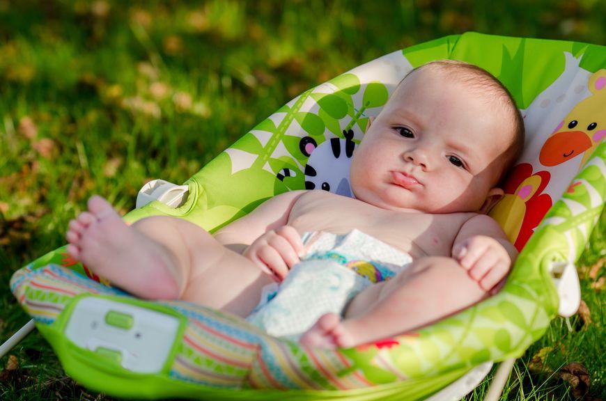 Baby in der Babywippe im Garten