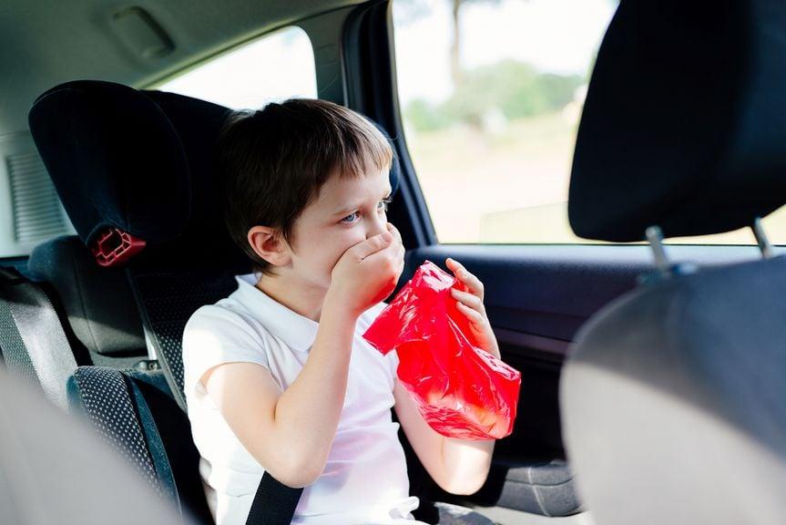 Kind im Auto mit der Hand vor dem Mund und einem Sack