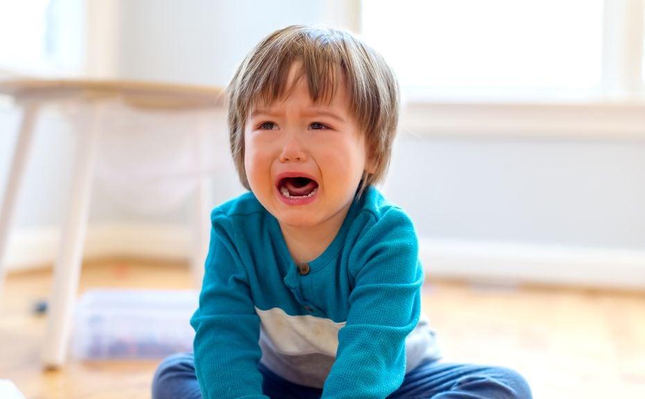 Kind sitzt auf dem Boden und weint