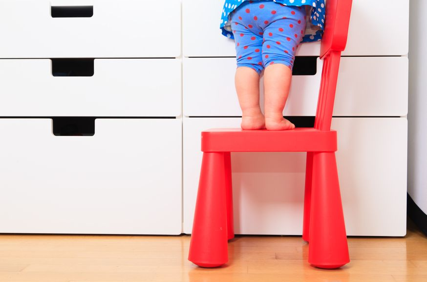 Kind steht auf einem Stuhl