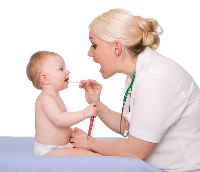Kinderärztin untersucht den Mund