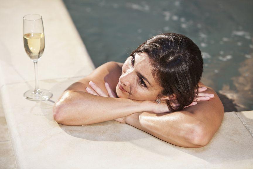 Frau am Poolrand mit einem Glas Sekt