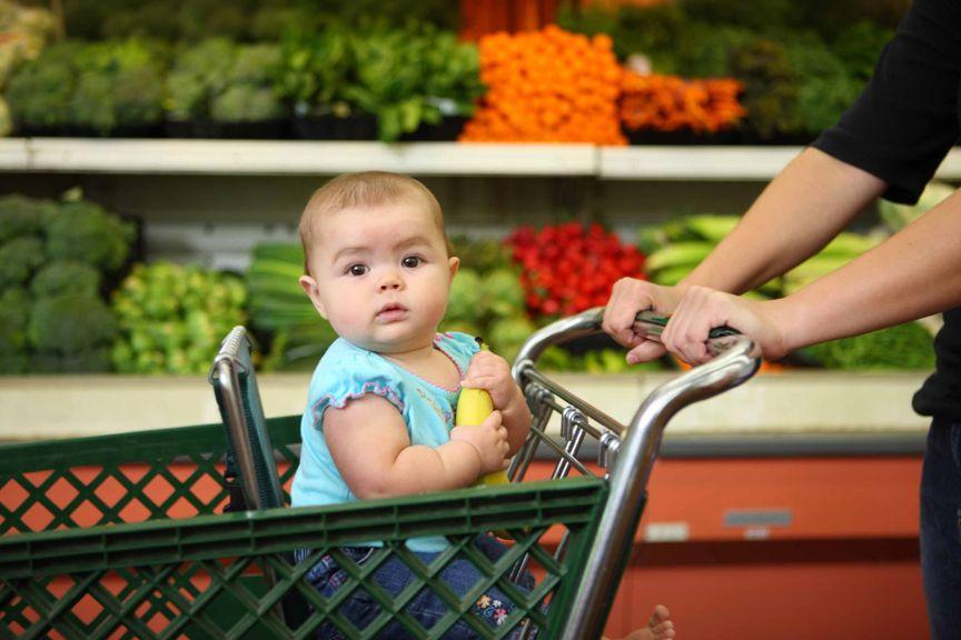 Baby sitzt im Einkaufswagen in der Gemüseabteilung