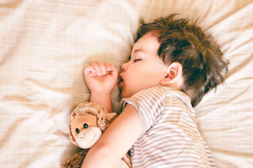 Kind schläft mit Affe im Arm