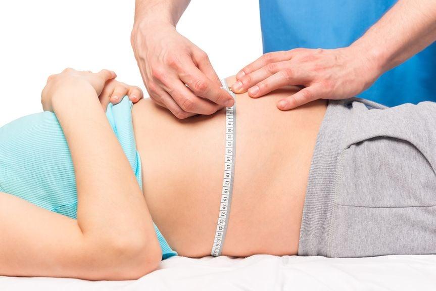 Frauenarzt misst den Bauch einer Schwangeren