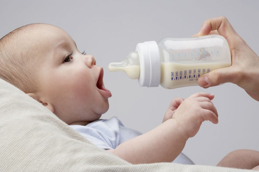 Baby öffnet den Mund um aus der Flasche zu trinken