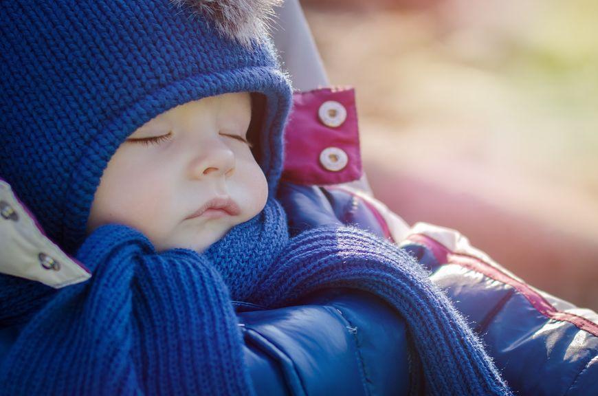 Baby schläft draussen in Winterkleidung