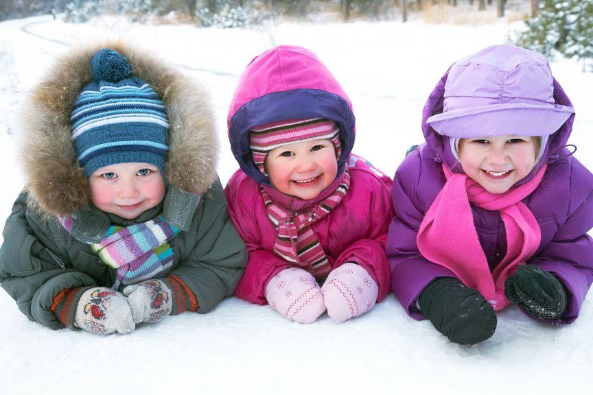 drei Kinder bäuchlings im Schnee