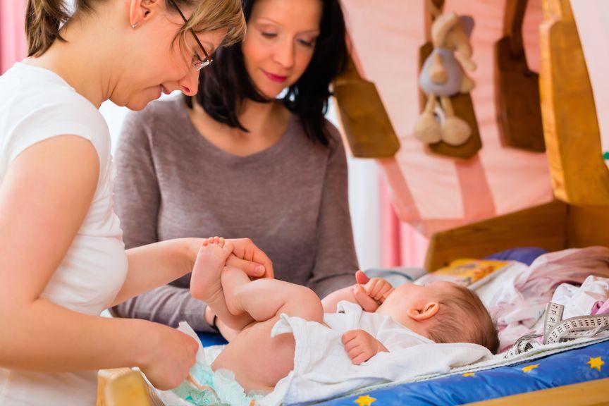 Hebamme wickelt das Baby beim Hausbesuch