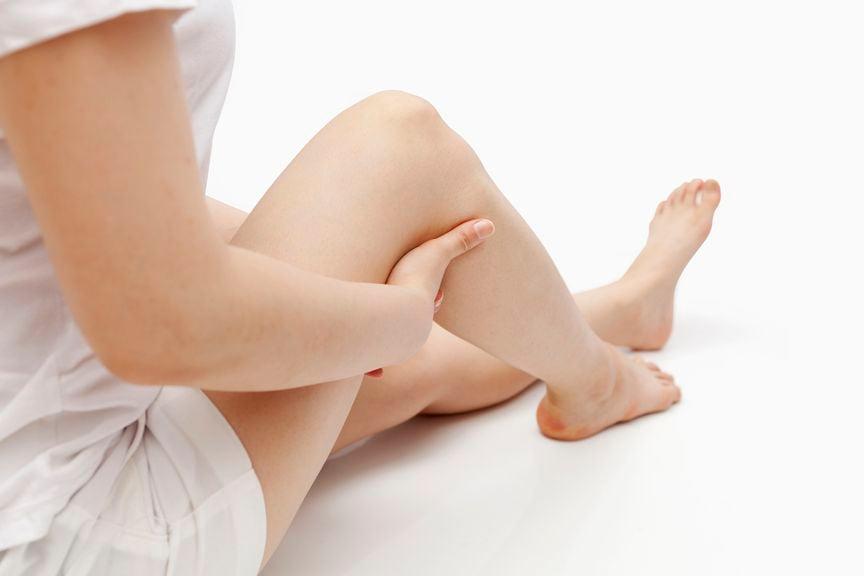 Frau hält sich das Bein unterhalb vom Knie