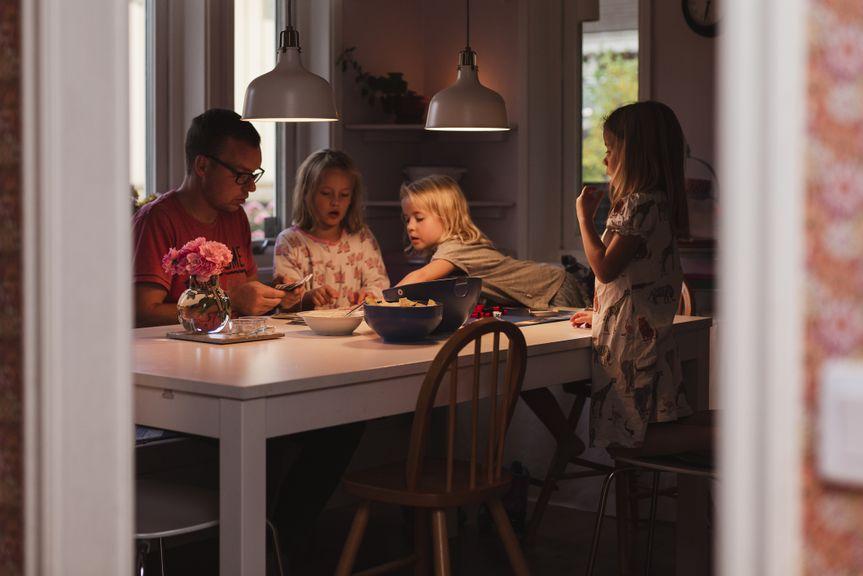 Vater mit drei Mädchen am Esstisch