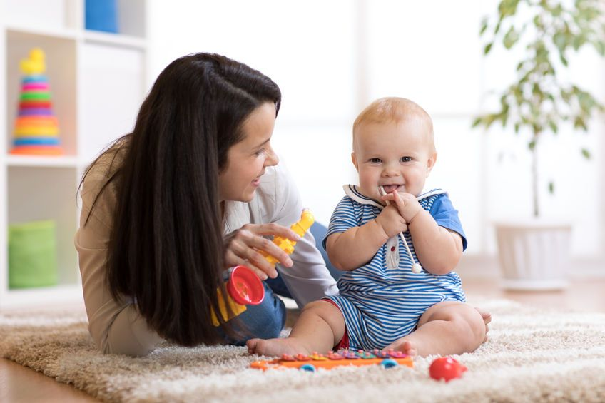Mutter und Baby spielen auf dem Teppich in einem hellen Kinderzimmer