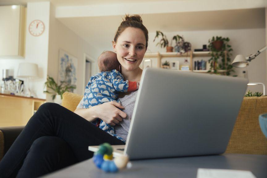 Mutter mit Neugeborenem am Laptop