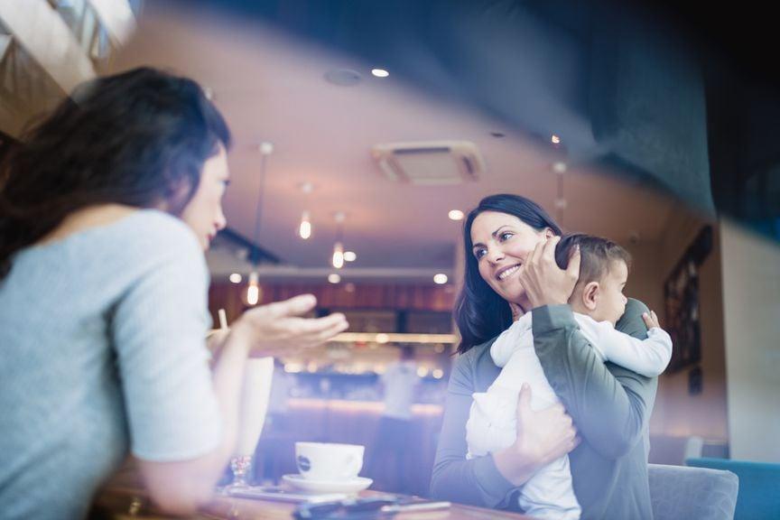 Mutter mit Baby im Gespräch in einem Kaffee