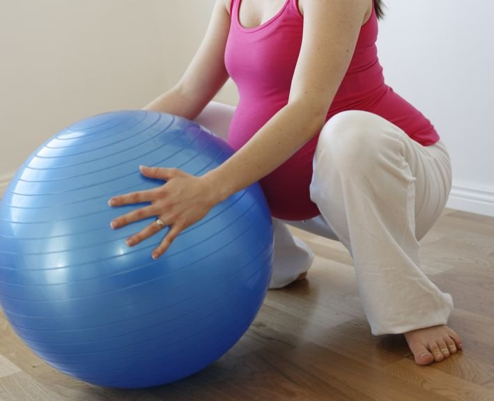 Schwangere in der Hocke mit Gymnastikball