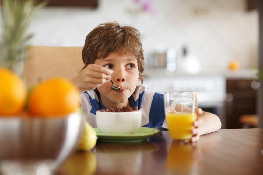 Kind mit Müsli und Orangensaft zum Frühstück