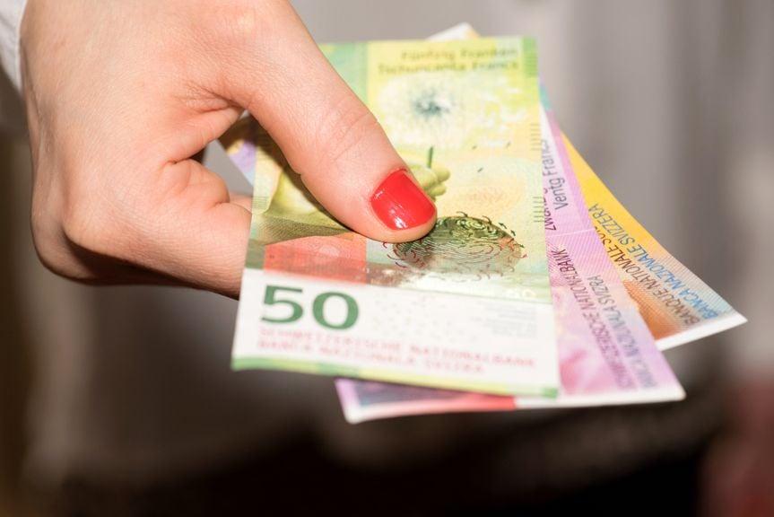 Hand mit Schweizer Banknoten