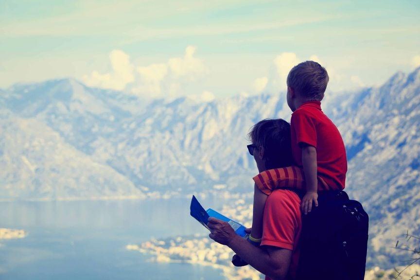 Vater mit Sohn auf den Schultern an einem Bergsee