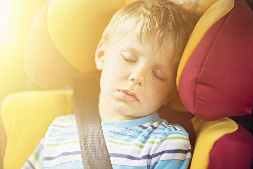Kind schläft im Autositz