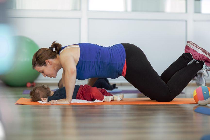 Mutter turnt auf Gymnastikmatte, Baby liegt unter ihr