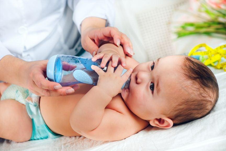 Baby trinkt aus dem Schoppen