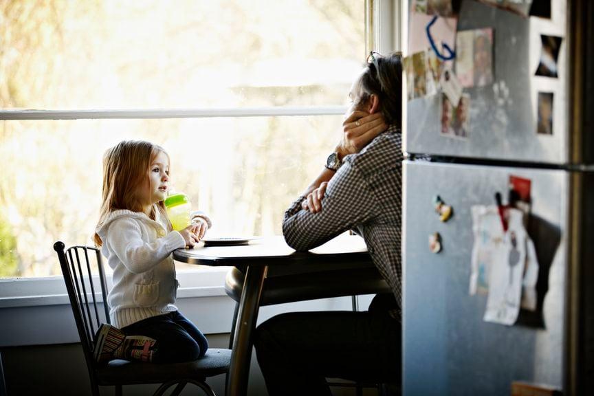 Kind sitzt mit Vater am Tisch