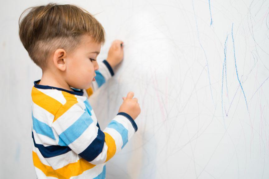 Kleiner Junge malt die Wand an
