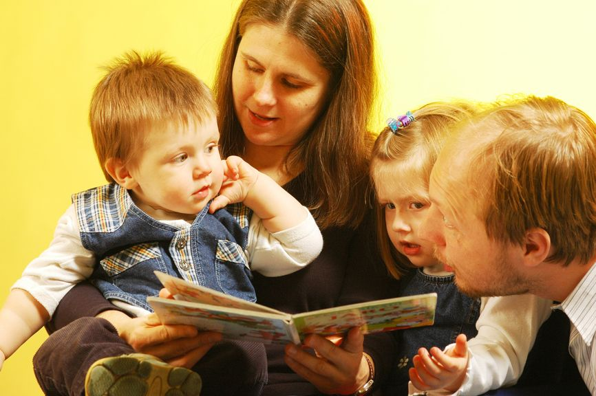 Vorlesezeit: Eltern und Kinder mit einem Bilderbuch