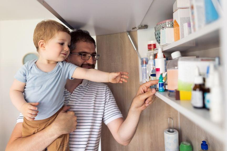 Vater hält  Sohn auf dem Arm und nimmt Medikament aus der Hausapotheke