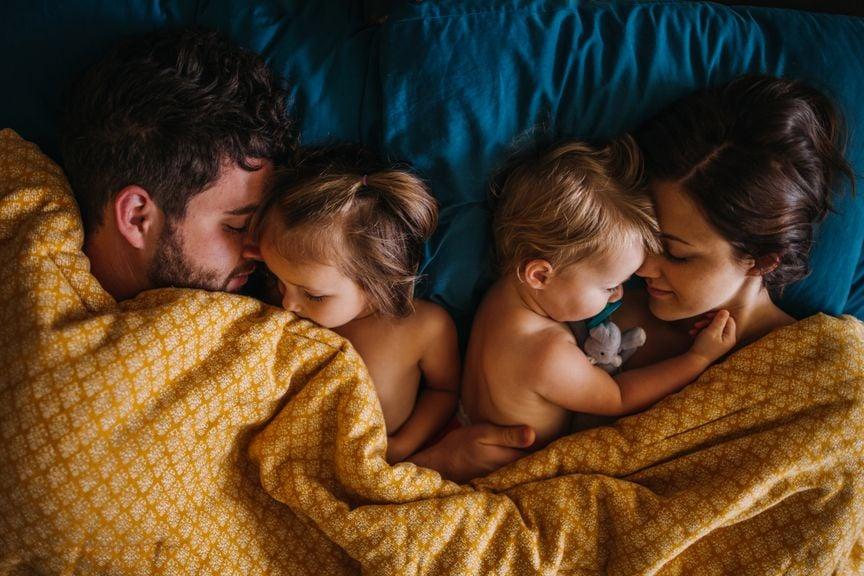 Eltern mit zwei Kindern im Familienbett
